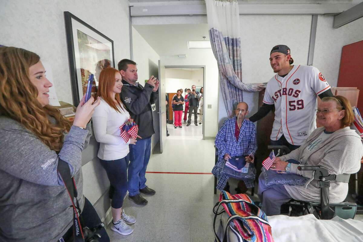 Astros pitcher and World Series Champion Joe Musgrove has his photo taken with Veteran Curtis Kirkland and his wife Jewan at the Michael E. DeBakey VA Medical Center Thursday, Nov. 9, 2017, in Houston. Musgrove and members from the Astros Foundation honored Veterans before Veterans Day. The Astros distributed gifts to the patients, including handmade cards from local elementary school students. ( Steve Gonzales / Houston Chronicle )
