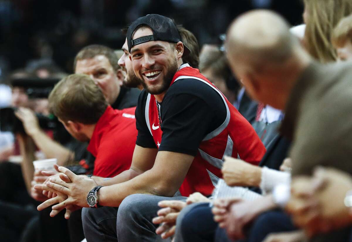 Houston Astros center fielder George Springer smiles at a fan as he sits courtside during a Rockets-Cavs game this season.