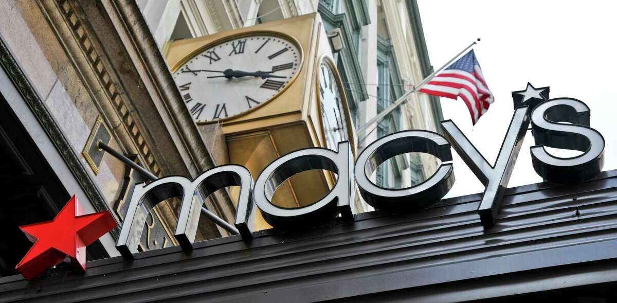 This Tuesday, May 2, 2017, photo shows corporate signage at Macy's flagship store in Manhattan, in New York. Macy's Inc. reports earnings Thursday, Nov. 9, 2017. (AP Photo/Bebeto Matthews)