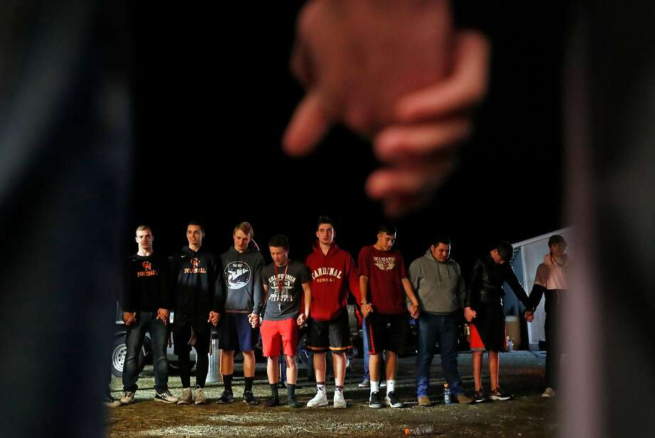 Cardinal Newman players pray before a team dinner hosted by Dave and Kelly Carroll, the parents of sophomore Cassidy, in Santa Rosa. Photo: Scott Strazzante, The Chronicle