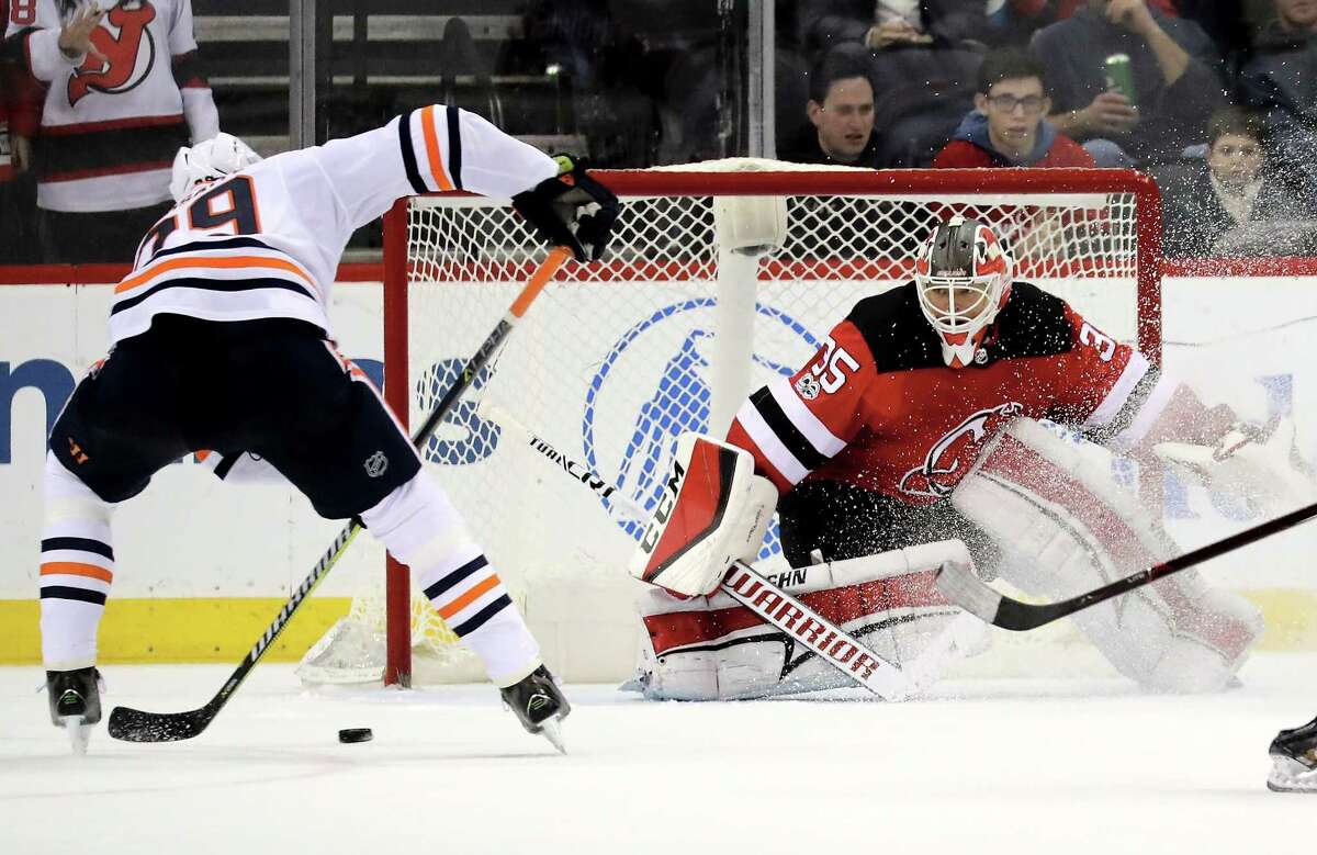 NEWARK, NJ - NOVEMBER 09: Leon Draisaitl #29 of the Edmonton Oilers scores the game winning goal in overtime as Cory Schneider #35 of the New Jersey Devils defends on November 9, 2017 at Prudential Center in Newark, New Jersey. (Photo by Elsa/Getty Images) ORG XMIT: 775040789