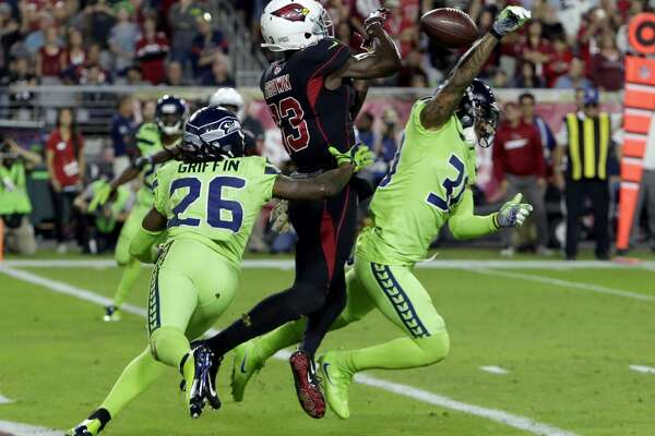 Seattle Seahawks defensive back Bradley McDougald, right, breaks up a pass intended for Arizona Cardinals wide receiver Jaron Brown (13) as cornerback Shaquill Griffin (26) pursues during the second half of an NFL football game, Thursday, Nov. 9, 2017, in Glendale, Ariz. (AP Photo/Rick Scuteri)