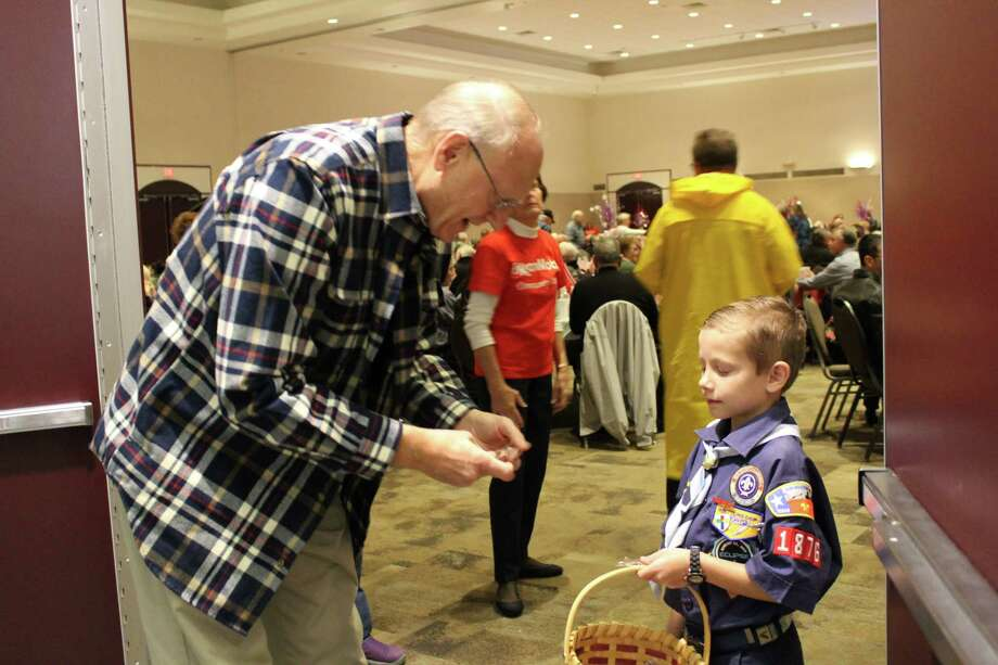 Houston Boy Scout Graham Clark hands a flag pin to a local veteran at Harris County Pct. 4 Commissioner Jack Cagle's Salute to Veterans on Wednesday, Nov. 8. Photo: Julie Silva