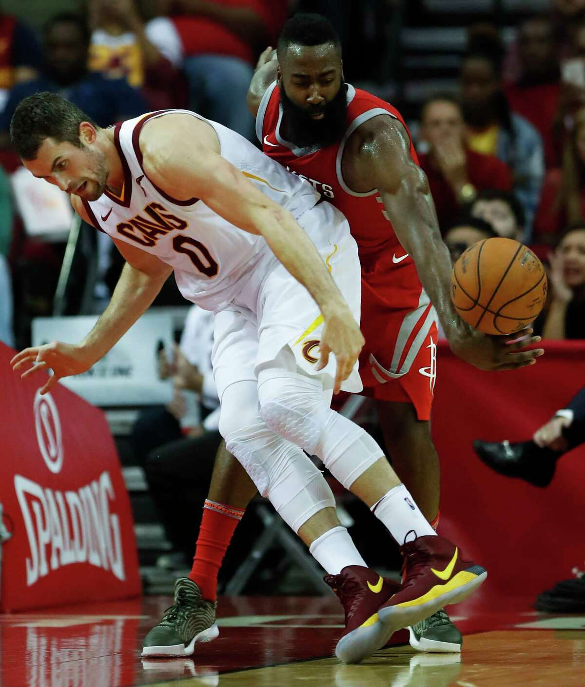 Rockets guard James Harden, right, pulls a surprise attack from behind to steal the ball away from Cavaliers forward Kevin Love during the first half at Toyota Center on Thursday night.