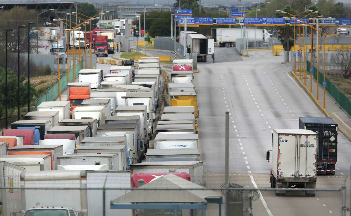 Two trucks, right, leave the United States as a long line of traffic waits to enter the U.S. from Mexico one morning at the World Trade Bridge in Laredo. The traffic is usually reversed in the evening.