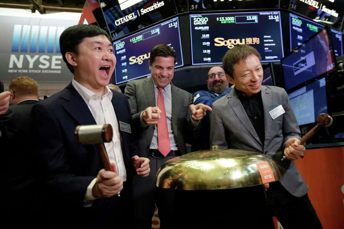 Sogou Inc. CEO Xiaochuan Wang, left, and company Chairman Charles Zhang, right, ring a ceremonial bell as their IPO begins trading, on the floor of the New York Stock Exchange, Thursday, Nov. 9, 2017. New York Stock Exchange President Tom Farley is at center. (AP Photo/Richard Drew)
