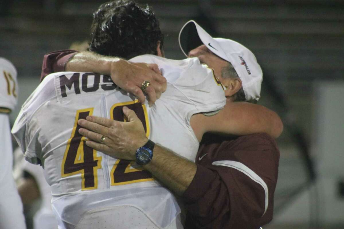 Linebacker Race Moser receives a district championship hug from one of his coaches, following the team's 42-24 triumph Thursday night.