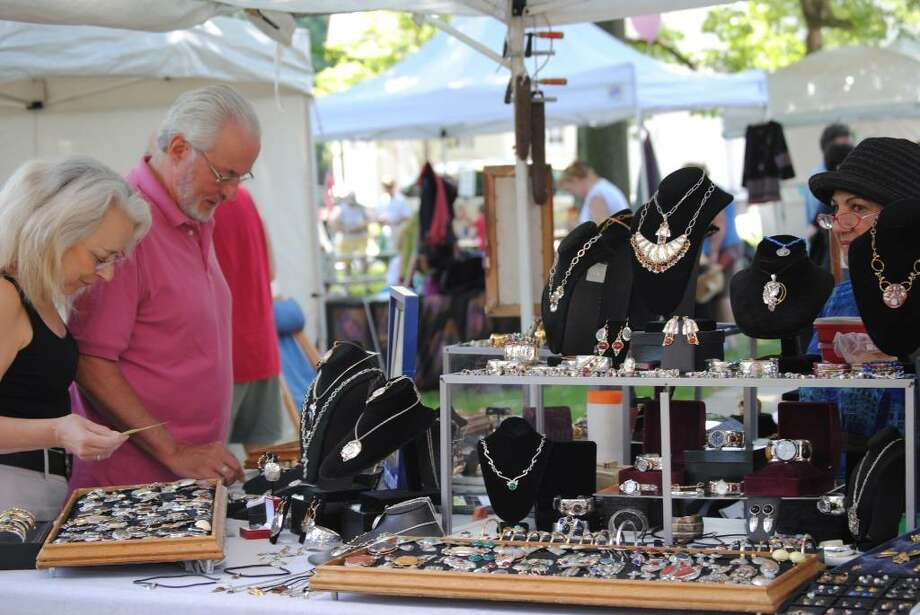 Gail Caprio and Mel Barr, both of Bridgeport, browse through the selection of jewelry hand-made by the husband of Barbara Booth, right. Booth was one of several artisans who set up booths on Town Green Saturday for the Fairfield Chamber of Commerce's annual craft show. The show will be open Sunday, June 26, too. Photo: Gary Jeanfaivre / Fairfield Citizen
