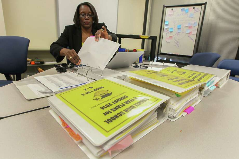 Chavez High Schoo Administrators Mrs. Stephanie Crook is in the process of transfering six binders of students records and course requests for next years seniors Friday, April 21, 2017, in Houston. This is the slow march of technological change through the public schools. Chavez High School is just now planning to adopt a digital platform for scheduling students, which has long been an arduous task of data entry and matching requirements with transcripts. This time of year, administrators are in the middle of that process. ( Steve Gonzales  / Houston Chronicle ) Photo: Steve Gonzales, Staff / © 2017 Houston Chronicle