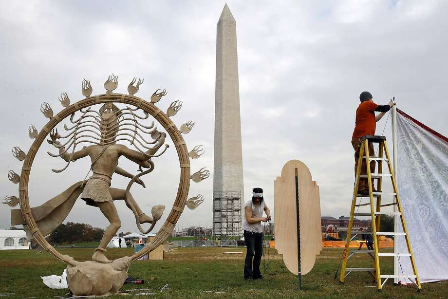 Jaye Brotherton (center), of Jamestown, Colo., and Ben Harper work on the installation of artwork Thursday for Catharsis on the Mall. The event runs through Sunday in Washington. Photo: Jacquelyn Martin, Associated Press