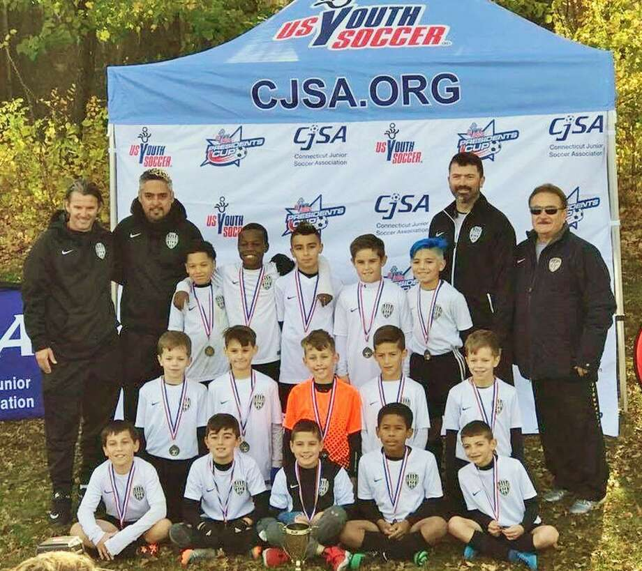 The Middletown Magic 2007 Boys won the CJSA CT Cup over Nov. 4 Suffield 3-1. Shown are (all from left), bottom row, James Wilson, Evan Stone, Brendan Burns, Julian Kuye and Ryan Quinn; middle row, Charlie Lechowicz, Avery Cameron, Tyler Hahn, Jacob Nardelli and Joseph Lechowicz; front row, Goran Vasic, Middletown Youth Soccer director of coaching; Hector Ballesteros, head coach Jaden Behm, Elijah Robinson, Adam Dagamesh, David Aresco, Jeffrey Savini, assistant coach Christopher Stone and MYS President Frank Marchese. Photo: Contributed Photo