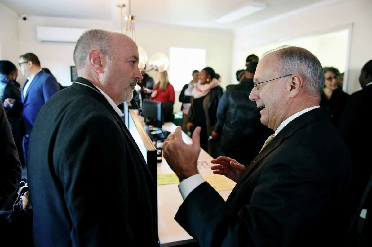 Troy Mayor Patrick Madden, left, and CDPHP President and CEO Dr. John Bennett, right, chat during a ribbon cutting event for the new TRIP on Tenth facility where local residents can get access to affordable housing and health care on Friday morning, Nov. 10, 2017, in Troy, N.Y. Troy Rehabilitation & Improvement Program and CDPHP have partnered on the program that will allow local residents to meet face-to-face with a community health specialist; learn about free or low-cost health insurance options; get help scheduling a doctor or dentist appointment; talk to a nurse; attend a health screening or be connected with wellness resources. (Will Waldron/Times Union)