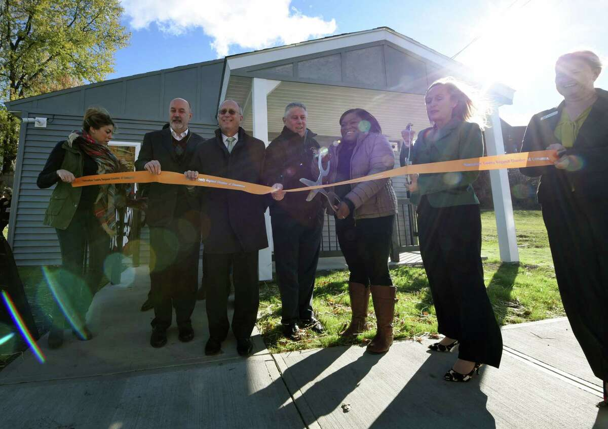Eleana Allen, daughter of late Emanuel Pompey, cuts the ribbon during an opening for the new TRIP on Tenth facility where local residents can get access to affordable housing and health care on Friday morning, Nov. 10, 2017, in Troy, N.Y. Troy Rehabilitation & Improvement Program and CDPHP have partnered on the program that will allow local residents to meet face-to-face with a community health specialist; learn about free or low-cost health insurance options; get help scheduling a doctor or dentist appointment; talk to a nurse; attend a health screening or be connected with wellness resources. (Will Waldron/Times Union)