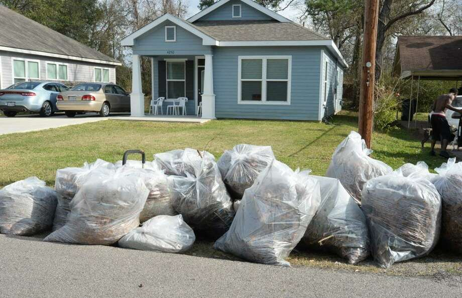 A collection of bags full of leaves and limbs lie at the foot of a lawn ready for pickup. Photo: File Photo