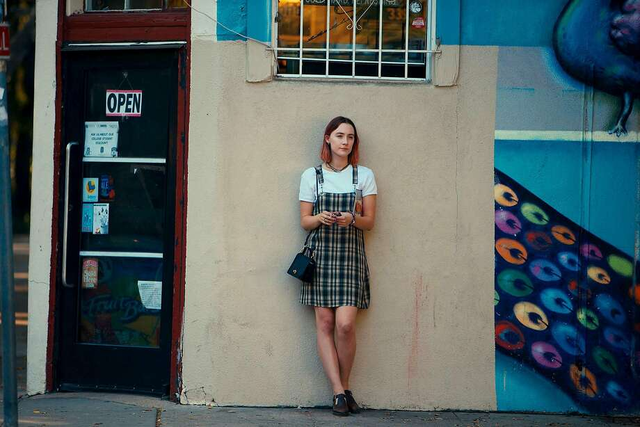 """Saoirse Ronan poses for a """"Lady Bird"""" promo shot in front of a colorful mural. Photo: Merie Wallace, A24"""