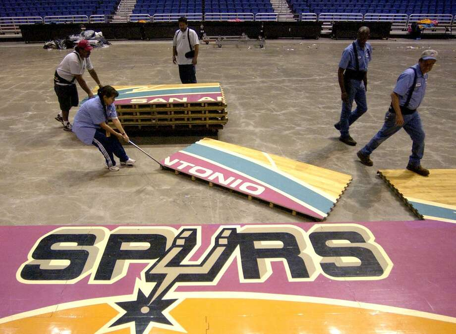 The Alamodome conversion crew works Thursday afternoon May 15, 2002 to pull the Spurs' basketball floor out of the Alamodome for the last time. The floor will be sold and used elsewhere. Photo: William Luther /San Antonio Express-News / SAN ANTONIO EXPRESS-NEWS