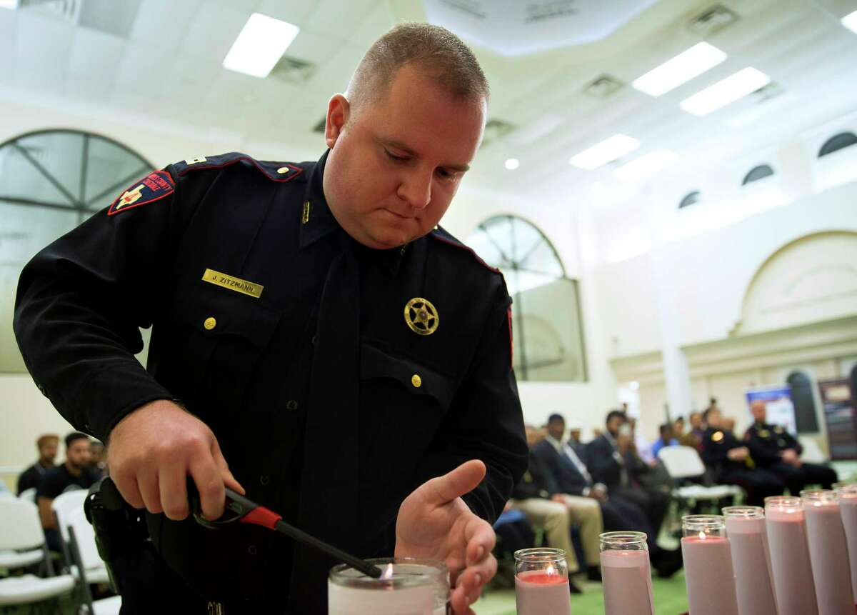 Captain Jonathan Zitzman of Mark Herman Precinct 4 Constable's Office lights a candle during a vigil remembering victims of violence, most recently the attacks in New York City and Sutherland Springs, at the Baitus Samee Mosque on Tuesday, Nov. 7, in Houston. (Annie Mulligan / Freelance)