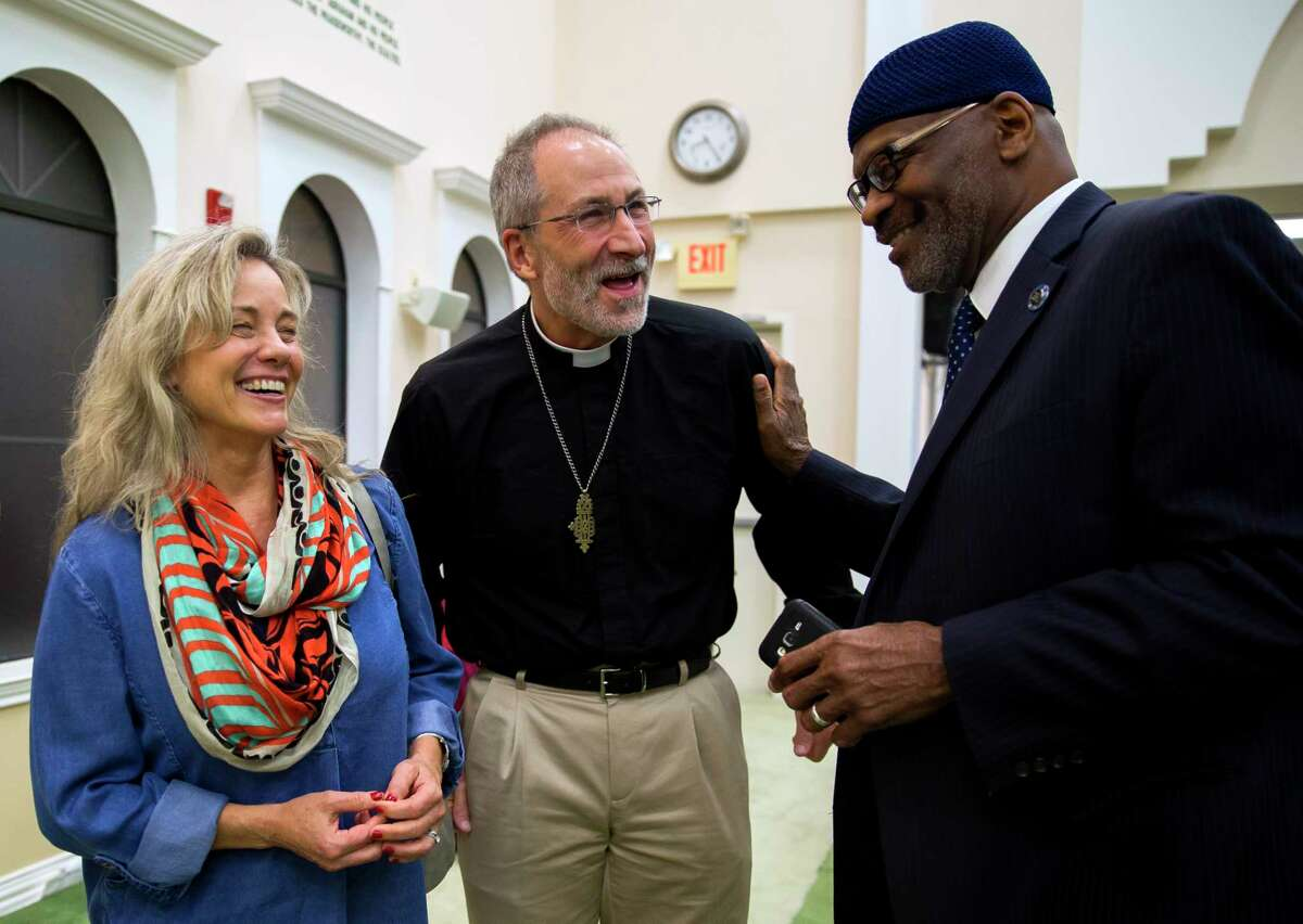 Kipp Richter and Rev. Bill Richter of Good Shepherd Episcopal Church chat with Mustafaa Carroll last week at an event to remember victims of violence held at Baitus Samee Mosque.