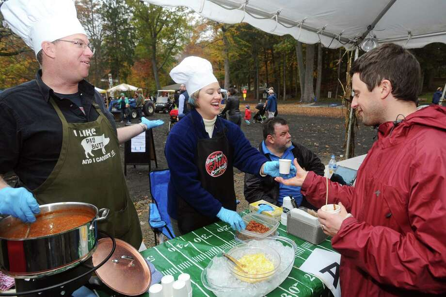 Brian and Erin Ash smile as they serve their Ash Family Chili to Tim Ley, of Fairfield, during the 10th annual Stamford Charity Chili Cookoff at the Stamford Museum and Nature Center on Sunday, Nov. 5, 2017. Photo: Michael Cummo / Hearst Connecticut Media / Stamford Advocate