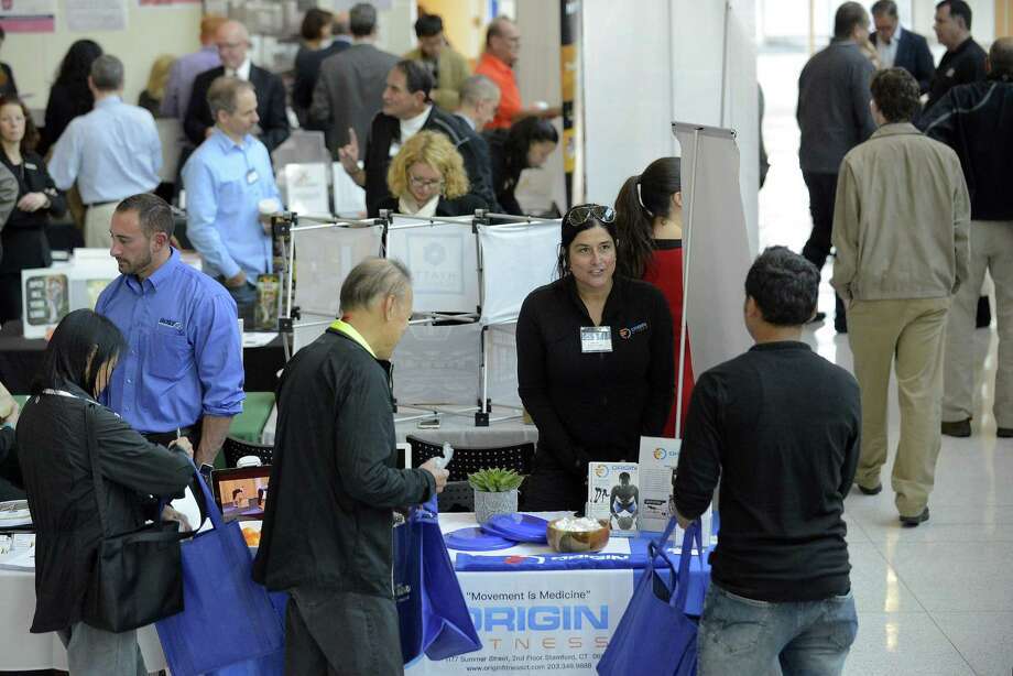 Jenna Brien, Marketing Director for Origin Fitness of Stamford speaks with attendees at the Stamford, Greenwich and Greater Norwalk chambers of commerce tabletop expo at UConn-Stamford campus on Nov. 17, 2016. Photo: Matthew Brown / Hearst Connecticut Media / Stamford Advocate