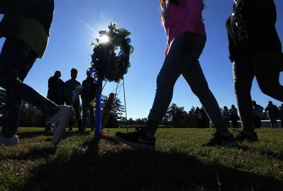 Kountze Intermediate students walk Friday past a wreath arranged for Trintin Glenn, 12, who was accidentally shot and killed on Wednesday. The students participated in a balloon release behind the school that morning. Glenn's family members can be seen behind the wreath. Photo taken Friday, November 10, 2017 Guiseppe Barranco/The Enterprise Photo: Guiseppe Barranco, Photo Editor / Guiseppe Barranco ©