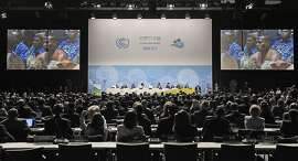FILE - In this Monday, Nov. 6, 2017 file photo, Native people from Fiji sit in the convention center during the opening of the COP 23 Fiji UN Climate Change Conference in Bonn, Germany. The US is participating in the talks, but experts say the U.S. position and President Donald Trump's comments could weaken efforts to curb global warming. (AP Photo/Martin Meissner, File)