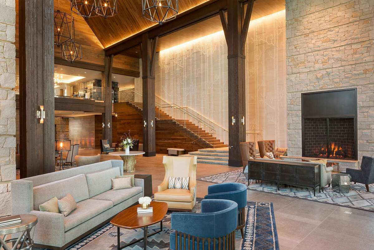 A lofty walnut-paneled ceiling and carved limestone walls add to the grandeur of the Great Room at the Lodge at Edgewood Tahoe.