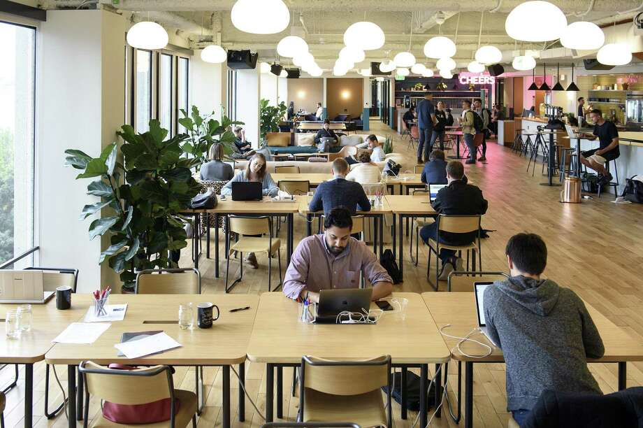 "Workers in October 2017 at a WeWork location in San Francisco, which provides shared office space and other amenities on a membership basis. At a retail mall in Portland, Ore., GGP has created space for a WeWork facility as it looks to convert its properties into ""lifestyle"" centers in the words of its CEO Sandeep Mathrani. Photo: Mike Short / Bloomberg / © 2017 Bloomberg Finance LP"