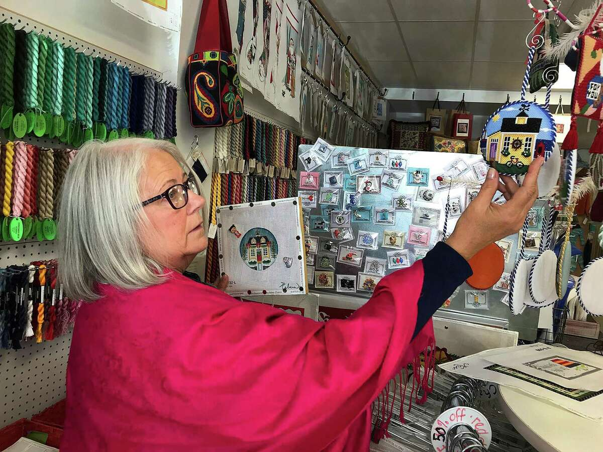 Mary Ellen Winnicki, a needlepoint instructor at A Stitch in Time in Bethel, Conn., shows what the finished product will look like during a class held Friday, Nov. 10, 2017.