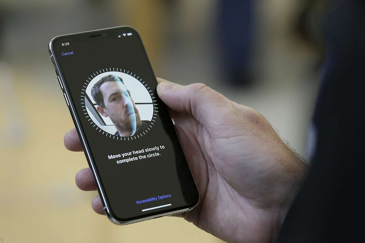 An Apple employee demonstrates the facial recognition feature of the new iPhone X.
