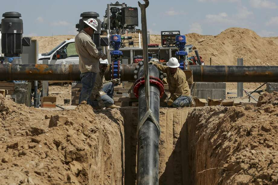 Contractors work to attach the end of a 20-mile water pipeline at Layne Christensen's new property Tuesday, July 18, 2017 in Pecos. The Woodlands based company is building a facility to supply water for hydraulic fracturing operations in the Delaware Basin. ( Michael Ciaglo / Houston Chronicle ) Photo: Michael Ciaglo/Houston Chronicle
