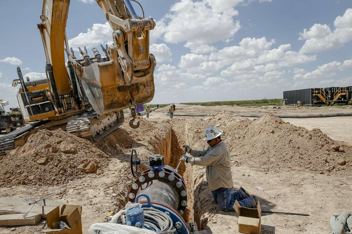 Contractors work to attach the end of a 20-mile water pipeline at Layne Christensen's new property Tuesday, July 18, 2017 in Pecos. The Woodlands based company is building a facility to supply water for hydraulic fracturing operations in the Delaware Basin. ( Michael Ciaglo / Houston Chronicle )