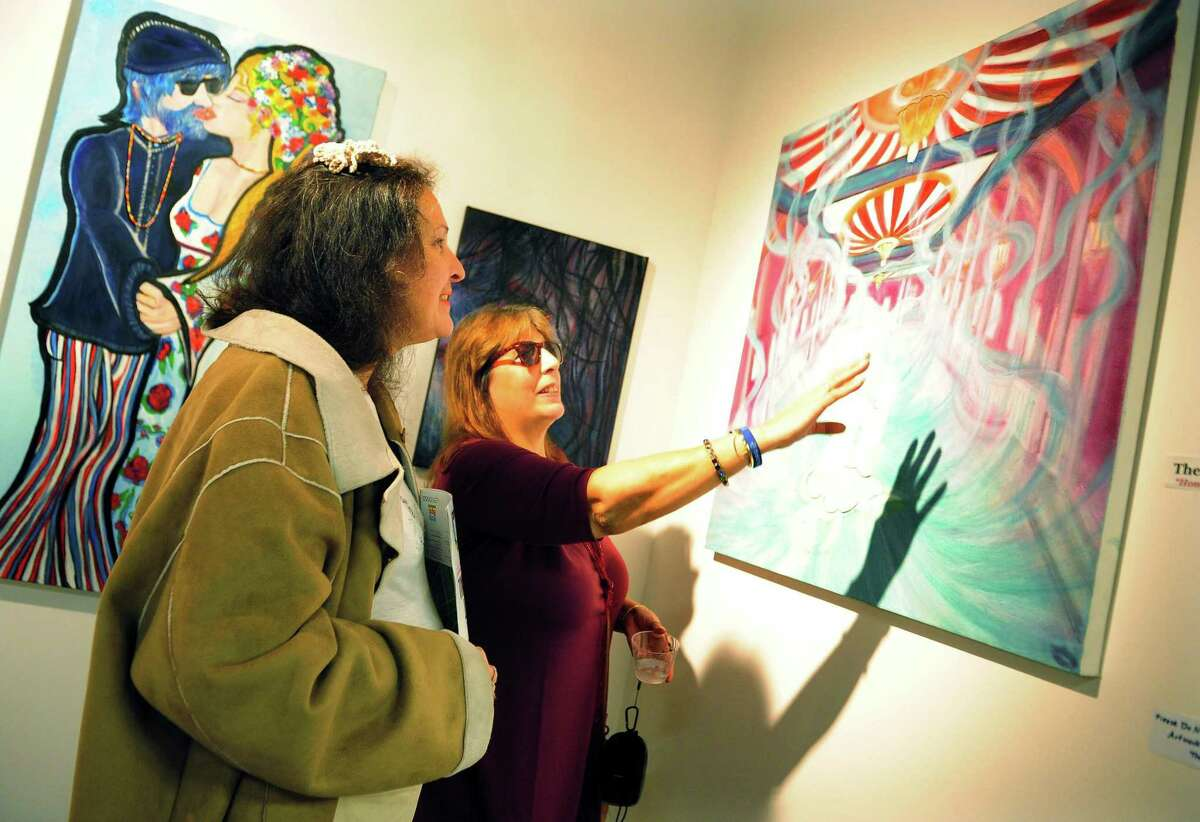 Artist Mia Lipstick, right, talks about one her paintings with friend Diane Kose during the 9th Annual Bridgeport Art Trail, which kicked off with an opening reception at the Read's ArtSpace