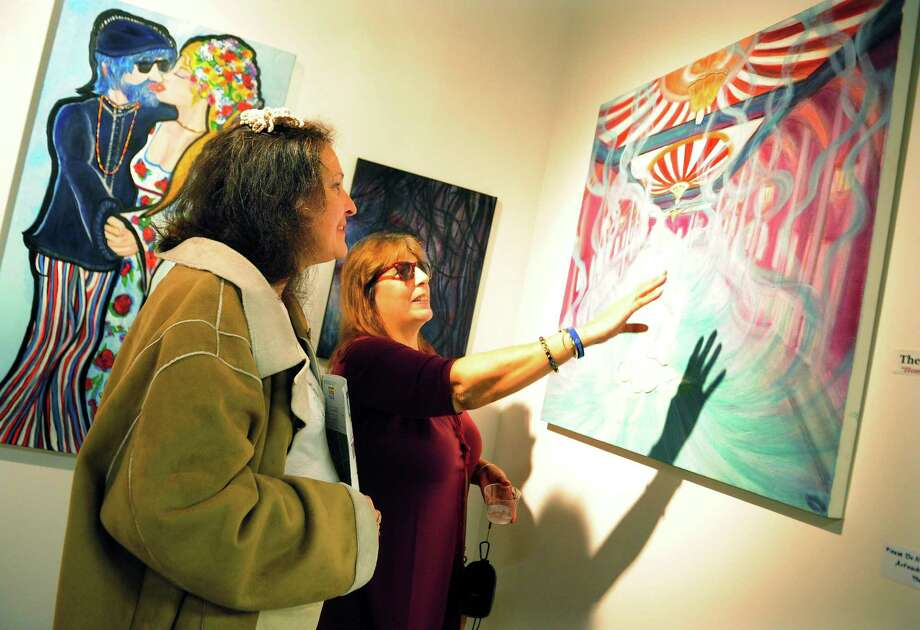 "Artist Mia Lipstick, right, talks about one her paintings with friend Diane Kose during the 9th Annual Bridgeport Art Trail, which kicked off with an opening reception at the Read's ArtSpace ""Artists Choose Artists""  exhibit in downtown Bridgeport, Conn., on Thursday Nov. 9, 2017. The Art Trail Open Studio Weekend runs through Sunday. For a full schedule of locations and events go to http://bridgeport-art-trail.org/arttrail-kickoff/ Photo: Christian Abraham / Hearst Connecticut Media / Connecticut Post"