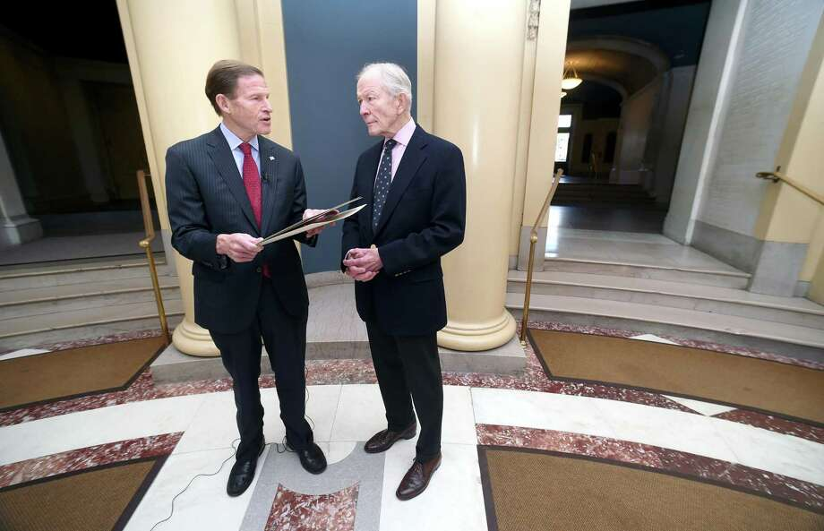 U.S. Sen. Richard Blumenthal, left, reads a resolution concerning a search for the San Antonio Rose B-17 Flying Fortress Heavy Bomber that went down during World War II in the Pacific Ocean and remains missing at Woolsey Hall in New Haven on November 10, 2017. At right is Doug Walker, son of Brigadier General Kenneth N. Walker, whose father was part of the crew of 11 aboard the plane when it went down under enemy fire. Photo: Arnold Gold / Hearst Connecticut Media / New Haven Register