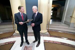 U.S. Sen. Richard Blumenthal, left, reads a resolution concerning a search for the San Antonio Rose B-17 Flying Fortress Heavy Bomber that went down during World War II in the Pacific Ocean and remains missing at Woolsey Hall in New Haven on November 10, 2017. At right is Doug Walker, son of Brigadier General Kenneth N. Walker, whose father was part of the crew of 11 aboard the plane when it went down under enemy fire.