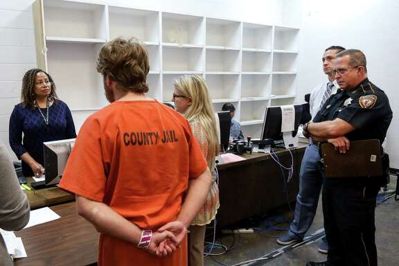 Judge Maria Jackson, left, Joshua Phanco, assistant district attorney, second from right, and a Harris County Sheriff's deputy, right, listen as Stephanie Martin, a defense attorney, center, speaks about her client's case in the 339th District Court, temporarily located in the Harris County Jail because of damage from Hurricane Harvey,  Friday, Oct. 27, 2017, in Houston.