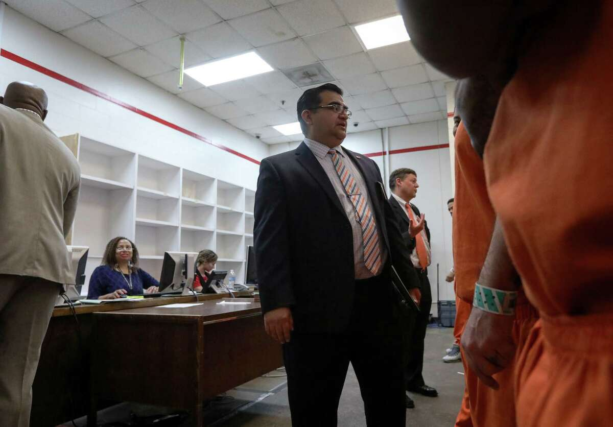 Carlos Rodriguez, center, a defense attorney, speaks with a client Oct. 27, 2017 in the 339th District Court, temporarily located in the Harris County Jail because of damage from Hurricane Harvey.