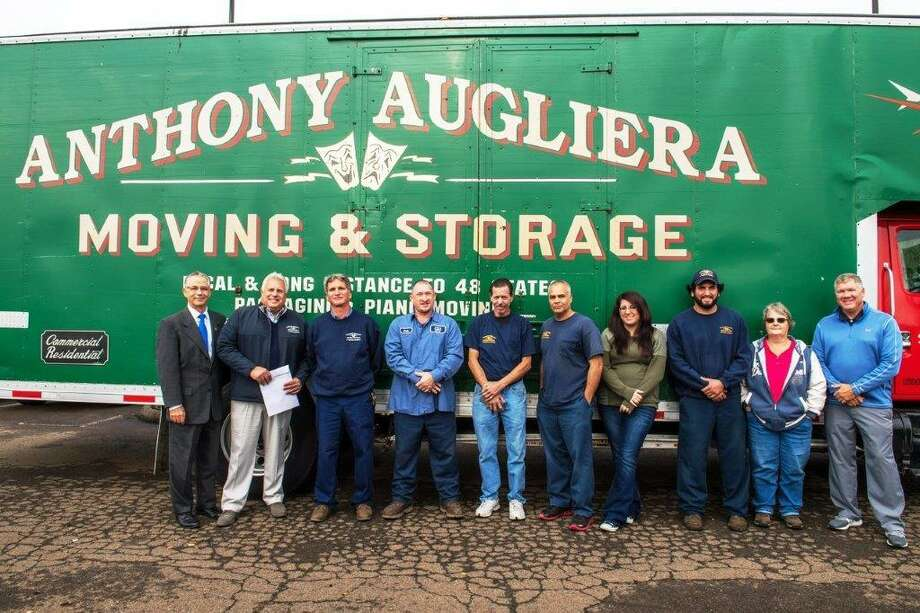 MOVING IN: East Haven Mayor Joseph Maturo Jr., left, is joined by Robert Augliera and several members of the Augliera family, as well as local officials and members of the Chamber of Commerce, at a ribbon-cutting ceremony recently for Anthony Augliera Moving & Storage, which relocated to town from West Haven. The 107-year-old company is located at 158 Commerce St. According to a release, the company used an existing 45,000-square-foot building as well as a newly constructed 12,000-square-foot foot building for all truck and equipment maintenance; Augliera also will add 40,000 square feet to the larger structure, the release said. Photo: Contributed Photo