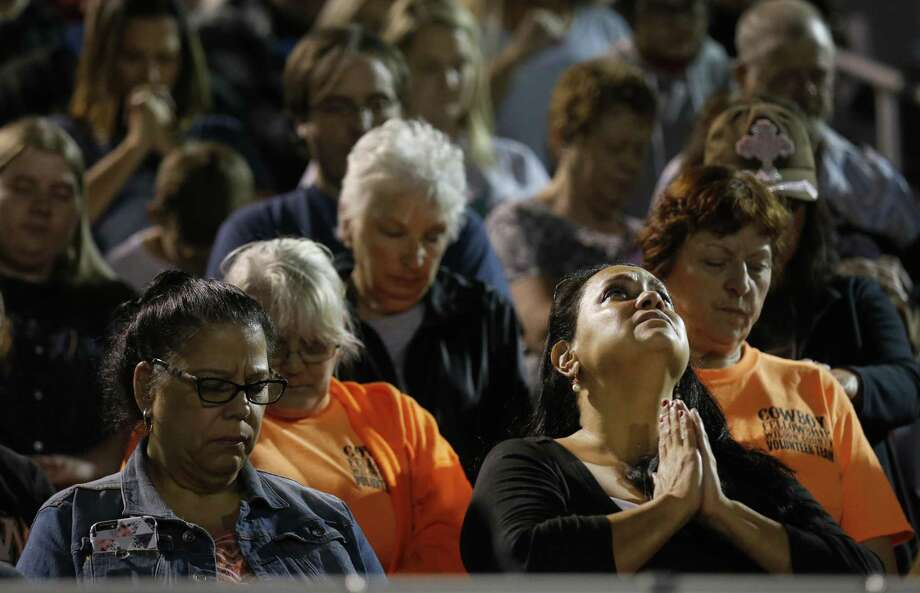 A mourner clasps her hands in prayer during a community memorial service at La Vernia High School's football stadium in the aftermath of the shooting tragedy at First Baptist Church in Sutherland Springs, Texas on Tuesday, Nov. 7, 2017. Photo: Kin Man Hui / ©2017 San Antonio Express-News