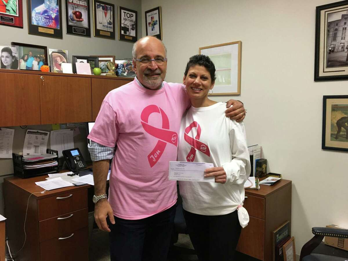 Pictured from left to right: Dr. Richard Zelkowitz, medical director of the Smilow Family Breast Health Center, accepts a donation from the ASF Sports & Outdoors store presented by Jennifer Bonitata.