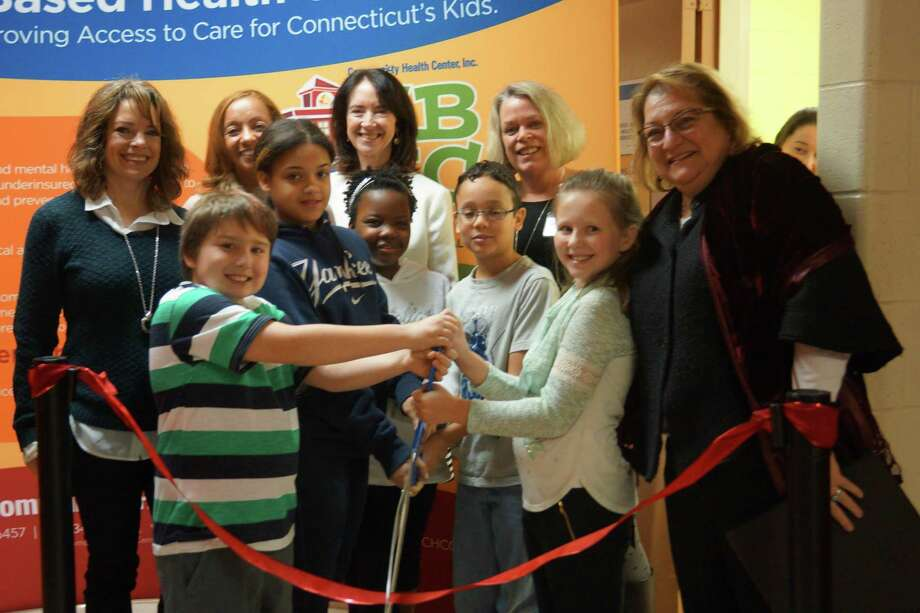 Community Health Center representatives celebrated the opening of a school health center at Pearson School in Winsted last week. Above, students help cut the ribbon during the event. Photo: Photo By Gabby Pantalena