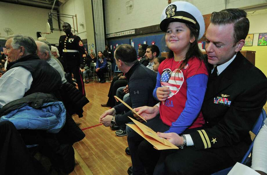 Marvin Elementary School third-grader Makaleigh Kline wears the hat of her uncle, Navy veteran John Fitzgerald, as students at the school recite poems, sing songs and present gifts to the local veterans in honor of Veterans Day Friday, Nov. 10. Photo: Erik Trautmann / Hearst Connecticut Media / Norwalk Hour