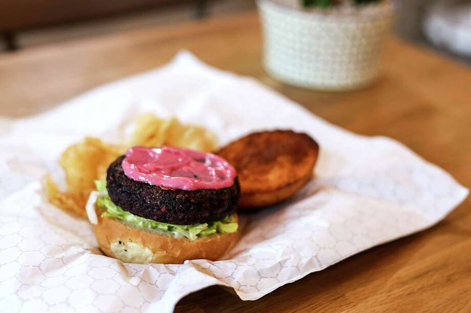 The new veggie burger from The Good Kind at The Pearl food hall uses a patty made in-house with quinoa, black rice, black beans, beets, carrots and onions. It's served on a specially baked potato bun from The Bread Box topped with toasted seaweed and chives, then dressed out with pink miso mayo and lettuce. Photo: Jacqueline Fierro /Courtesy Of Giant Noise