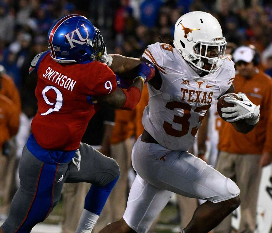 Texas running back D'Onta Foreman stiffarms Fish Smithson of Kansas at Memorial Stadium on Nov. 19, 2016 in Lawrence, Kansas. The Jayhawks upset the Longhorns 24-21. Photo: Ed Zurga /Getty Images