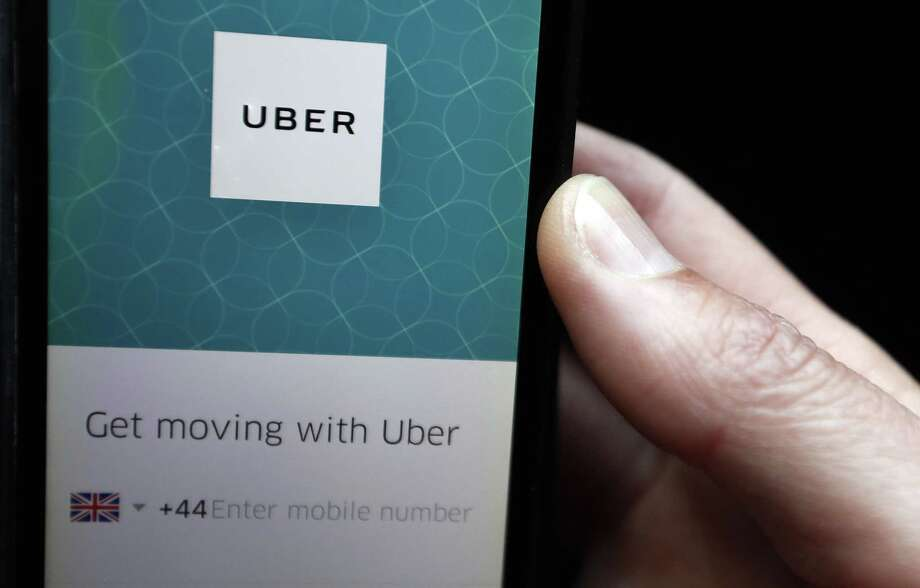 An Uber App is displayed on a phone in London. On Friday, Britain's Employment Appeal Tribunal ruled that drivers of the ride-hailing service are entitled to basic protections such as a guaranteed minimum wage and paid time off. Photo: Kirsty Wigglesworth /Associated Press / Copyright 2017 The Associated Press. All rights reserved.