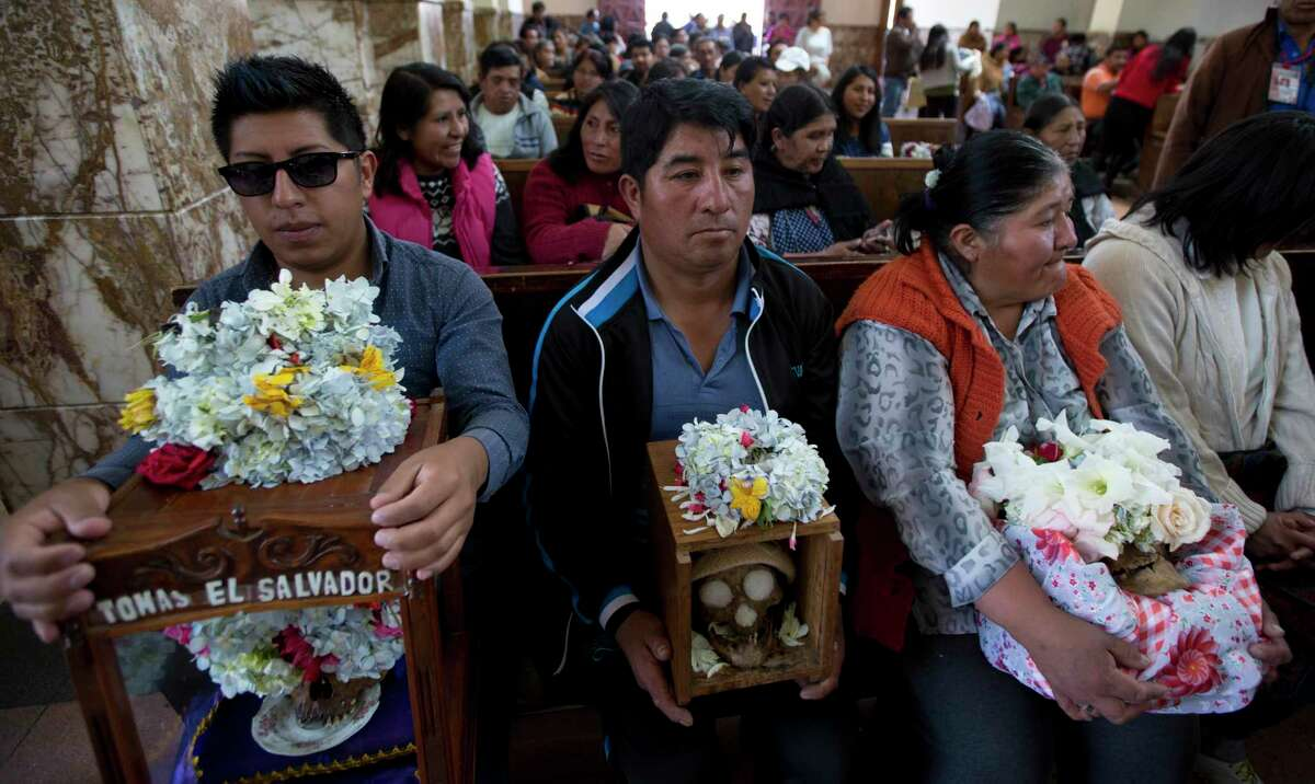 People carry decorated human skulls after praying inside at the General Cemetery chapel during the Natitas Festival in La Paz, Bolivia, Wednesday, Nov. 8, 2017. Celebrated a week after the Day of the Dead, Bolivians carry human skulls adorned with flowers to cemeteries asking for money, health, and other favors as part of a festival. (AP Photo/Juan Karita)