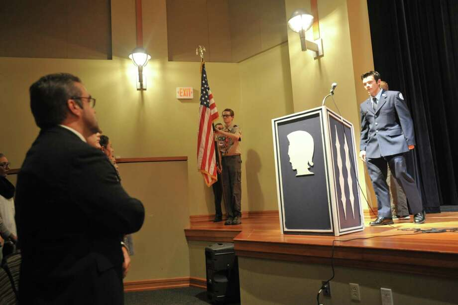 Lewis S. Mills High School students honored local veterans with a luncheon and assembly in honor of Veterans Day. Above, a guest approaches the podium during the assembly. Photo: Ben Lambert / Hearst Connecticut Media