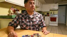 Army Sgt.1st Class Gabriel Monreal with medals he has received including a Purple Heart, two Bronze Stars and an Army Commendation Medal at his home Oct. 25. Monreal has served for twenty years including tours in both Iraq and Afghanistan. He lost his left leg in Afghanistan in 2010.