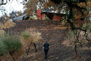 Security guard Joshua Antrim walks towards a damaged home on Bennett Lane in Calistoga, Calif. on Friday, Nov. 10, 2017 next door to the property where authorities believe the Tubbs Fire started. PG&E filed legal papers suggesting that third party electrical equipment, not theirs, may have been the cause of last month's deadly Tubbs Fire.